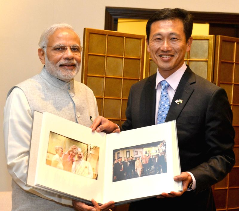 Prime Minister Narendra Modi being presented a photo album of his Singapore visit, before his departure from Singapore on Nov. 24, 2015. - Narendra Modi