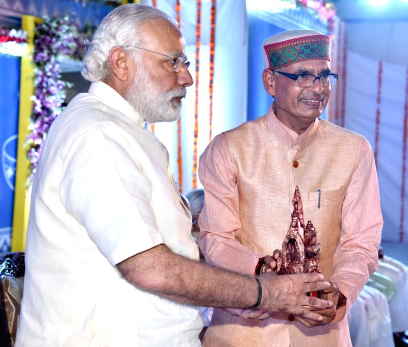 Prime Minister Narendra Modi being presented a memento by the Madhya Pradesh Chief Minister Shivraj Singh Chouhan, at the International Convention on Universal Message of Simhastha, in Ujjain ... - Narendra Modi and Shivraj Singh Chouhan
