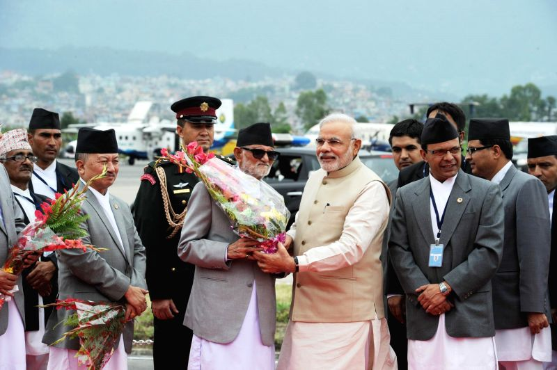 Prime Minister Narendra Modi being received by the Prime Minister of Nepal Sushil Koirala on his arrival, at Tribhuvan International Airport in Kathmandu, Nepal on Aug 3, 2014. - Narendra Modi