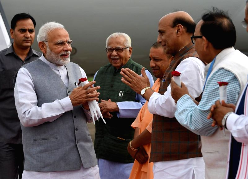 Prime Minister Narendra Modi being received by Uttar Pradesh Governor Ram Naik, Chief Minister Yogi Adityanath, Union Home Minister Rajnath Singh and state BJP chief Mahendra Nath Pandey on ... - Narendra Modi, Rajnath Singh and Mahendra Nath Pandey
