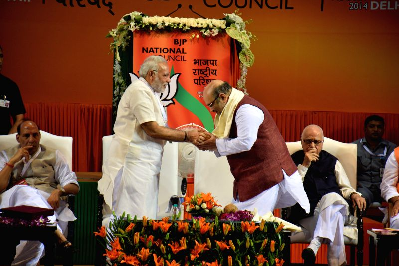 Prime Minister Narendra Modi congratulating newly appointed BJP President Amit Shah at the BJP National Council meeting in New Delhi on Aug. 9, 2014. - Narendra Modi