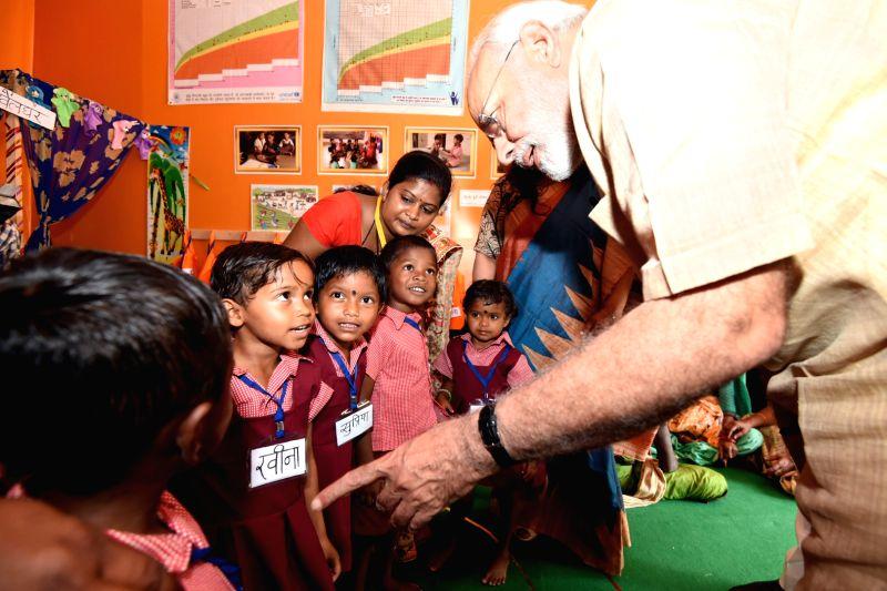 Prime Minister Narendra Modi interacts with beneficiary children of Poshan Abhiyan in Chhattisgarh's Jangla, on April 14, 2018. Also seen Chhattisgarh Chief Minister Raman Singh. - Narendra Modi and Raman Singh