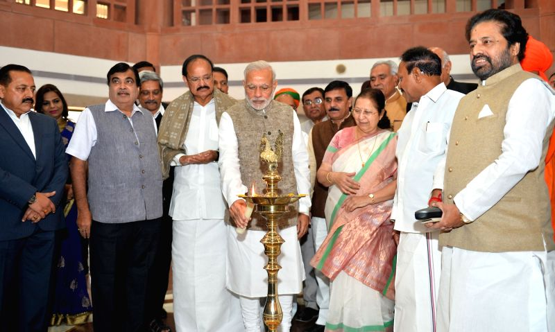 Prime Minister Narendra Modi lights the lamp to inaugurate an exhibition on making of the Constitution by the Constituent Assembly, at Parliament Library, in New Delhi on Nov 26, 2015. Also seen Lok ... - Narendra Modi, M. Venkaiah Naidu and Sumitra Mahajan