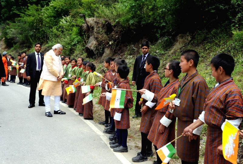 Prime Minister Narendra Modi meeting children who lined up waving flags to wish him goodbye along the road to the airport, in Thimphu, Bhutan on June 16, 2014.