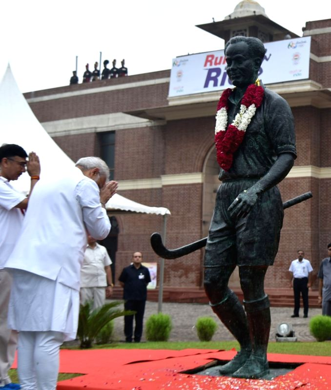 """Prime Minister Narendra Modi paying tributes to Major Dhyan Chand, at the flagging off ceremony of """"Run For Rio"""", at Major Dhyan Chand National Stadium, in New Delhi on July 31, ... - Narendra Modi and Rajiv Yadav"""