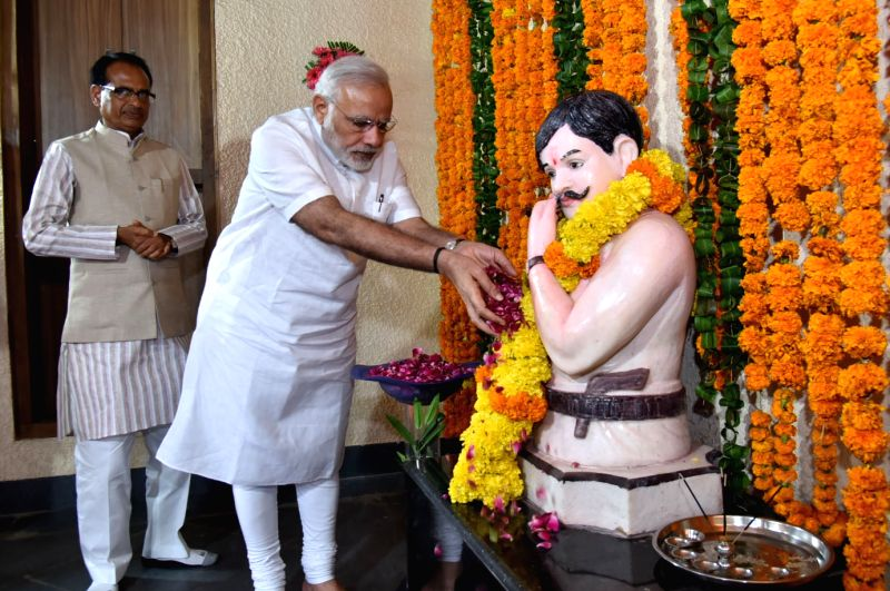 Prime Minister Narendra Modi pays floral tribute to Shaheed Chandrashekar Azad, in Bhabra village, Alirajpur district of Madhya Pradesh on Aug 9, 2016. Also seen Madhya Pradesh Chief ... - Narendra Modi and Shivraj Singh Chouhan