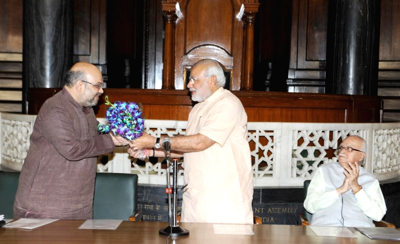 Prime Minister Narendra Modi presents a bouquet to the BJP chief Amit Shah during BJP Parliamentary Party meeting in New Delhi on July 31, 2014. Also seen BJP veteran L K advani. - Narendra Modi and Amit Shah