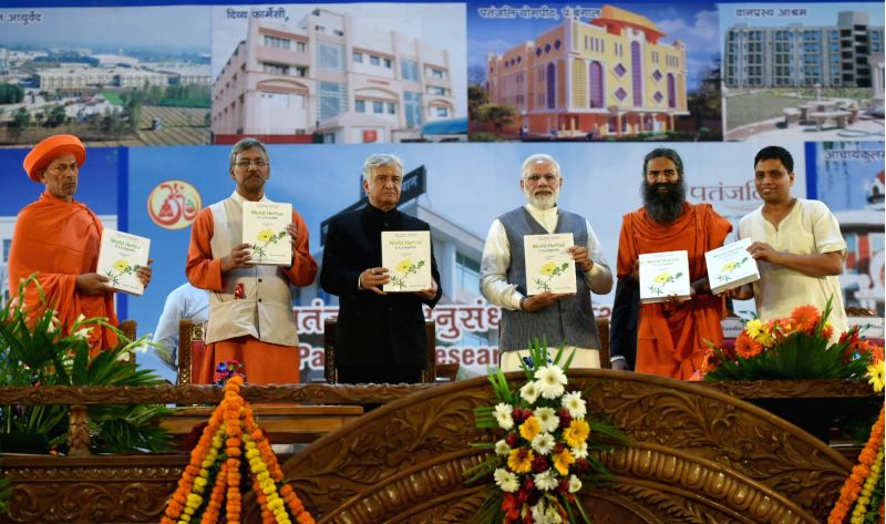 Prime Minister Narendra Modi releases World Herbal Encyclopedia at the inauguration of Patanjali Research Institute, in Haridwar, May 3, 2017. Also seen Uttarakhand Governor Dr. Krishan ... - Narendra Modi and Trivendra Singh Rawat
