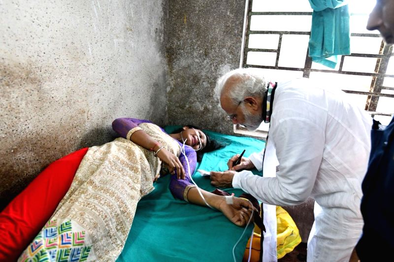 """Prime Minister Narendra Modi signs an autograph for a woman who among others, got injured when the portion of a tent collapsed during """"Kisan Kalyan"""" rally, in West Bengal's Midnapore ... - Narendra Modi"""
