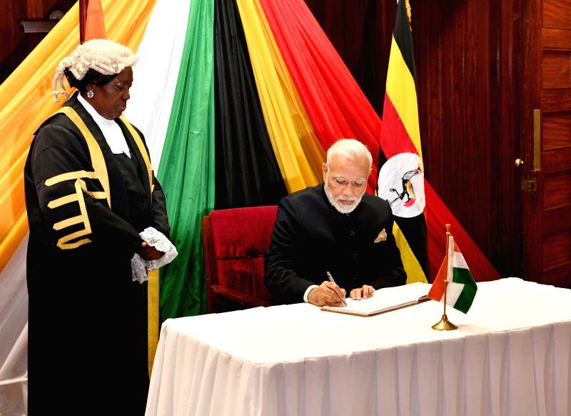 Prime Minister Narendra Modi signs the Visitors' Book at the Parliament of Uganda, in Kampala on July 25, 2018. - Narendra Modi