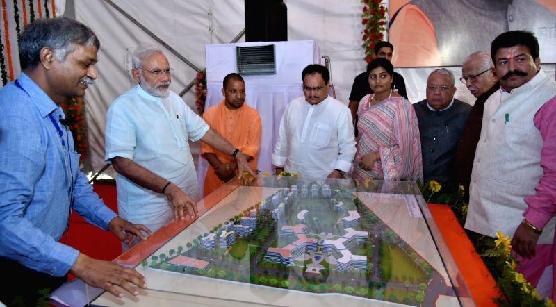 Prime Minister Narendra Modi watchs the model of AIIMS Gorakhpur, during the foundation stone laying ceremony of the AIIMS Gorakhpur and for the revival of Gorakhpur Fertilizer plant, at ... - Narendra Modi and J