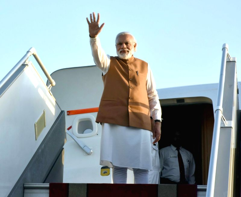 Prime Minister Narendra Modi waves before his departure from Tehran on May 23, 2016. - Narendra Modi