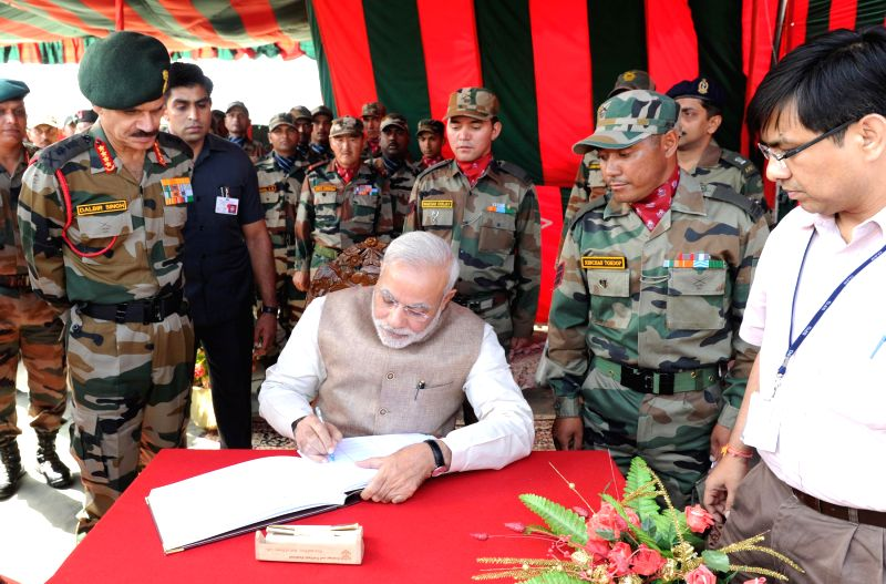 Prime Minister Narendra Modi writes in the Visitors Book at 14 Corps HQ at Leh on August 12, 2014. Also seen Chief of Army Staff, General Dalbir Singh. - Narendra Modi and Dalbir Singh