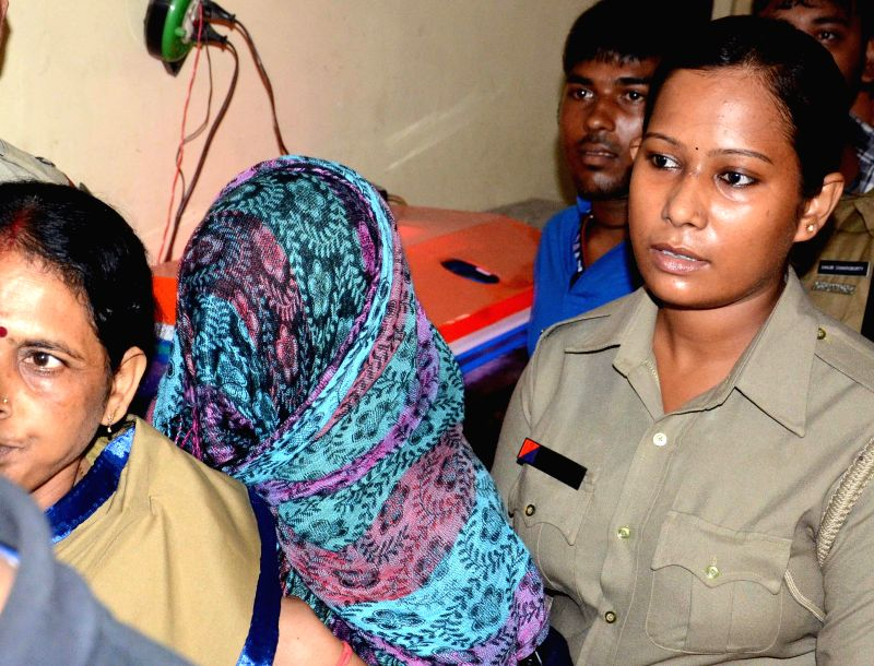 Private tutor Pooja Singh (face covered) arrested for torturing a 3-year old child, produced at Bidhannagar Nagar Court in Kolkata on July 26, 2014.