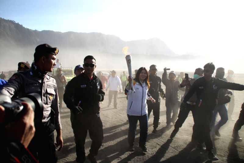 PROBOLINGGO, July 21, 2018 - Indonesian retired badminton athlete Susi Susanti (C) holds the Asian Games torch during the torch relay at the sand sea of Mount Bromo in Probolinggo, East Java, ...