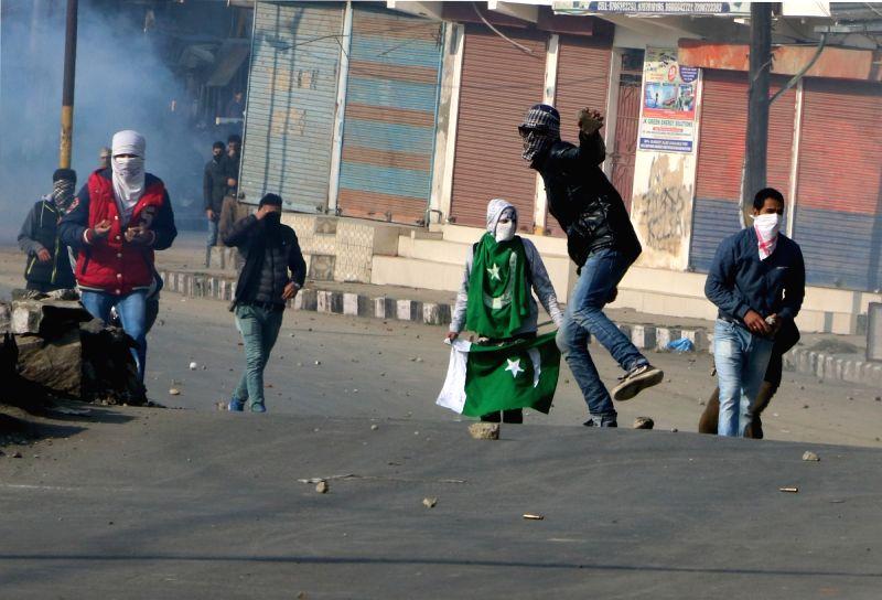 Protesters pelt stones on policemen after a protest against arrest of separatists turned violent  in Srinagar, on Nov 27, 2015.