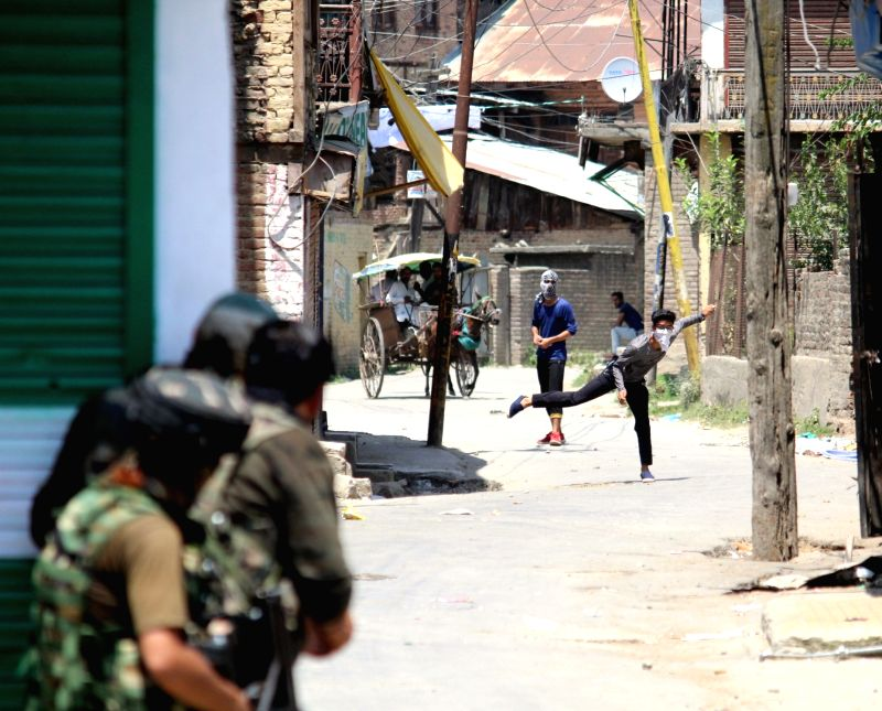 Protesters pelt stones on security personnel during a separatist-called shutdown in support of Article 35A that gives special powers to the state legislature, in Sopore, Jammu and Kashmir on ...