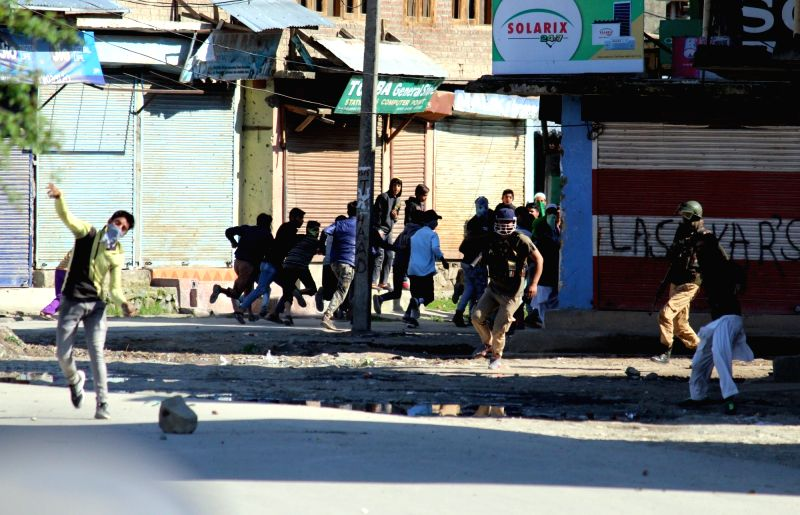 Protesters pelt stones on security personnel in Sopore of Jammu and Kashmir on April 13, 2018.