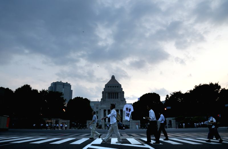 Protesters walk in front of the National Diet Building during a rally against the controversial security laws in Tokyo, Japan, June 24, 2015. About 30,000 people ...