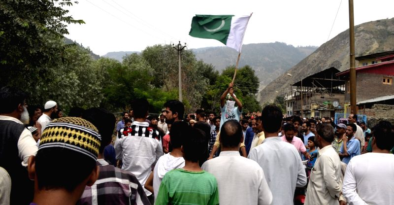 Protesters wave Pakistan flags during a demonstration in Baramulla on July 25, 2016.