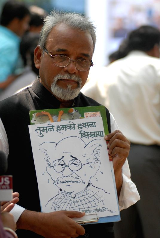 A admirer with Cartoonist RK Laxman's sketch paying his last respect at the cartoonist's funeral in Pune on Jan. 27, 2015.