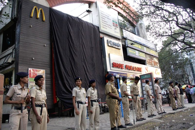 Policemen deployed near a fast food chain that denied a destitute child a snack in Pune, on Jan 20, 2015.