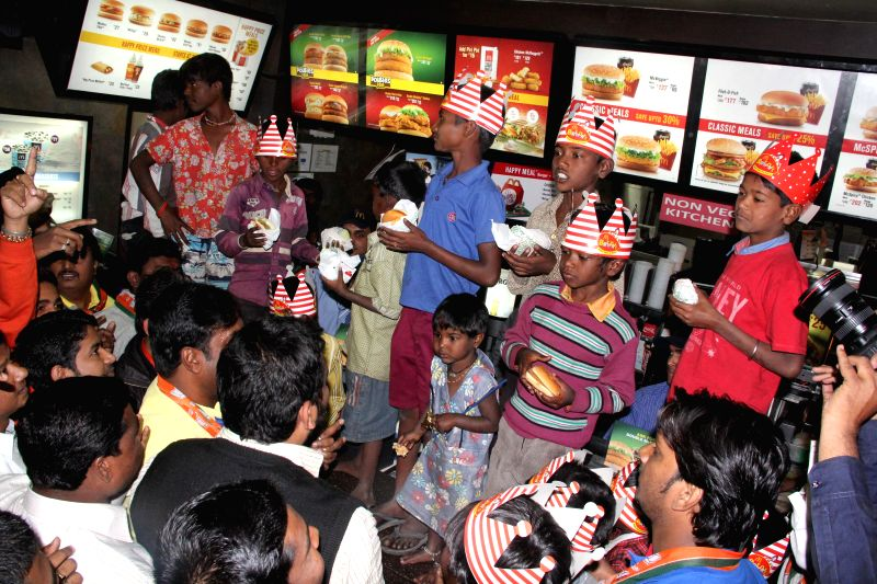 Underprivileged children enjoy themselves at one of the outlets of a fast food chain that recently denied a snack to a destitute child in Pune, on Jan 20, 2015. Their meal was sponsored by an ..