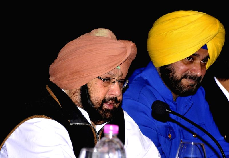 Punjab Chief Minister and Congress leader Captain Amarinder Singh addresses a press conference in Amritsar on Dec 7, 2017. Also seen Punjab Minister Navjot Singh Sidhu. - Amarinder Singh and Navjot Singh Sidhu