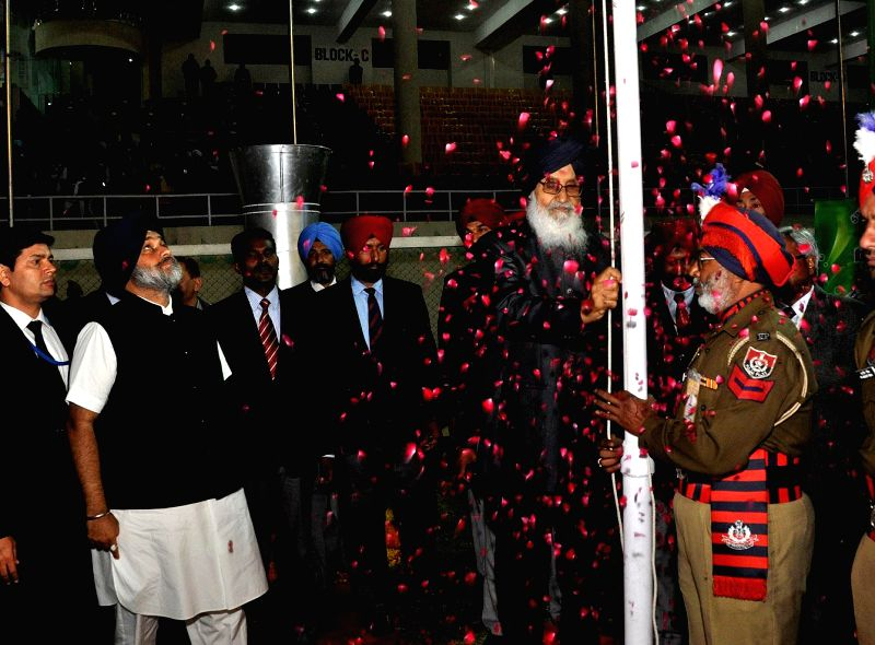 Punjab Chief Minister Parkash Singh Badal with Punjab Deputy Chief Minister Sukhbir Singh Badal hoisting the flag during the inaugural programme of fifth World Kabbadi Cup in Amritsar on Dec 6, 2014. - Parkash Singh Badal and Sukhbir Singh Badal