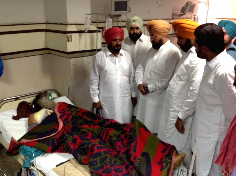 Punjab Congress chief and party's candidate from Gurdaspur Lok Sabha seat, Partap Singh Bajwa meets S. Roop Singh a congress supporter who was shot by alleged Shiromani Akali Dal workers last night, . - S. Roop Singh