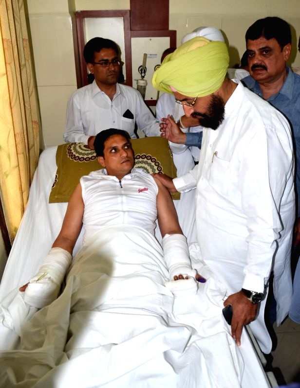 Punjab Congress chief Partap Singh Bajwa meets advocate Vaneet Mahajan who is admitted in the hospital after being fatally attacked in Amritsar on May 14, 2014.