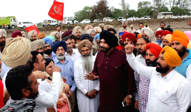 Punjab Minister Navjot Singh Sidhu interacts with farmers during his visit to a field where standing wheat crop were destroyed in a fire near Amritsar on April 23, 2017. - Navjot Singh Sidhu