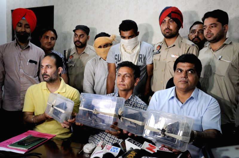 Punjab police personnel produce before press two alleged terrorists arrested in Amritsar on April 19, 2017.