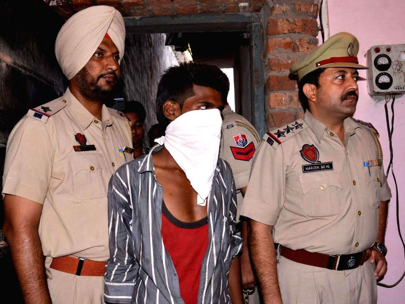 Punjab police personnel take away a person who allegedly killed his mother in Amritsar on July 4, 2014.
