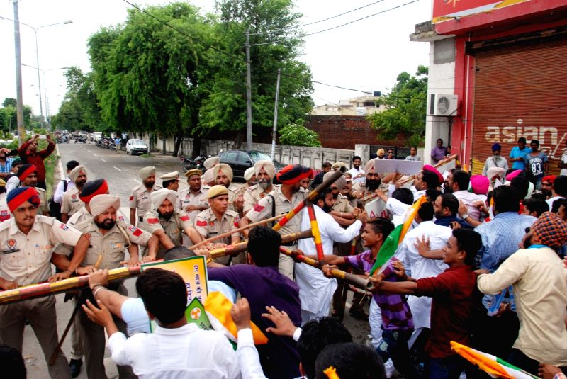 Punjab Police trying to stop the Congress workers during their protest against the state minister Anil Joshi outside his residence in Amritsar on July 23, 2016. - Anil Joshi