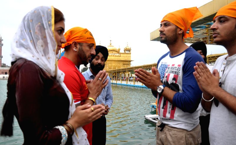 Punjabi singers and actors Jaswinder Singh Bains and Garry Sandhu with actress Parul Gulati at Golden Temple in Amritsar on May 12, 2014.