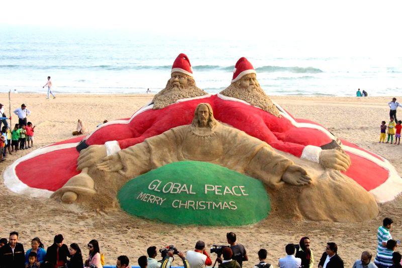 Renowned sand artist Sudarsan Pattnaik's sand sculpture calls for global peace on Christmas eve at Puri beach, Odisha on Dec 25, 2014.