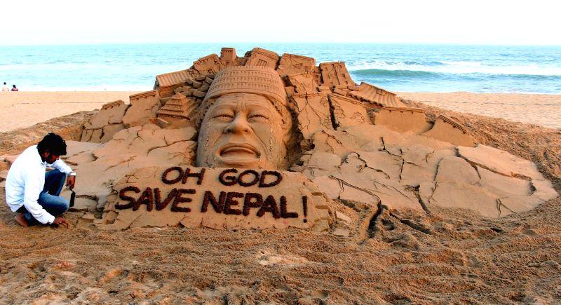 Renowned sand artist Sudarsan Pattnaik's creation reading `Oh God, Save Nepal!` at Puri beach, Odisha on May 12, 2015.