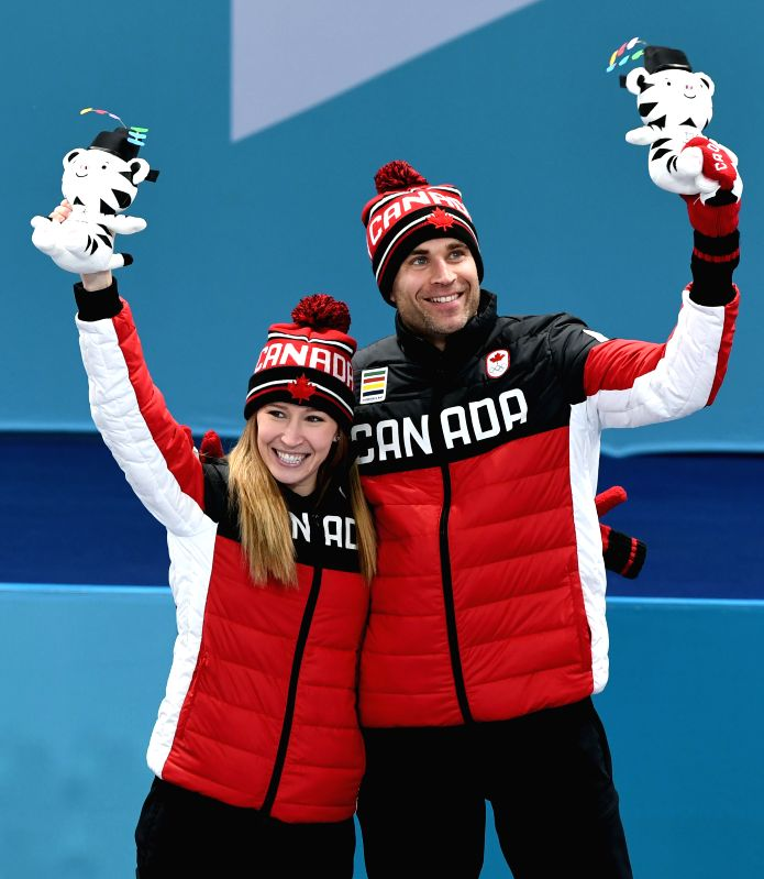 PYEONGCHANG, Feb. 13, 2018 - Kaitlyn Lawes (L) and John Morris of Canada celebrate after finishing the mixed doubles gold medal game of curling between Canada and Switzerland at the Pyeongchang 2018 ...