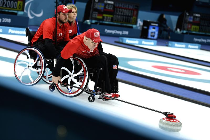 PYEONGCHANG, March 13, 2018 - Kirk Black (R) from the United States competes during the match between the United States and China at the mixed round robin session 10 of wheelchair curling at the 2018 ...