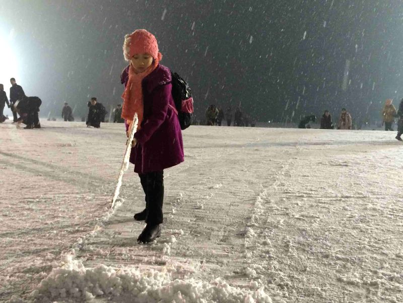 Pyongyang (DPRK): A student sweeps snow at the Mansudae Grand Monument in Pyongyang, the Democratic People's Republic of Korea (DPRK), Dec. 10, 2014. Pyongyang witnessed the first snow fall in this ..