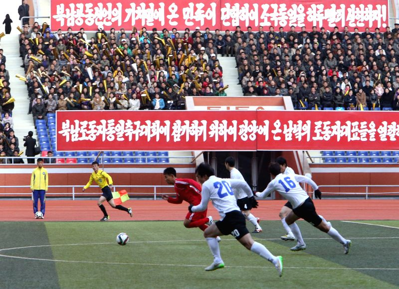 Football players from the Democratic People's Republic of Korea (DPRK) and the Republic of Korea (ROK) compete for the ball during the North-South workers' football ...