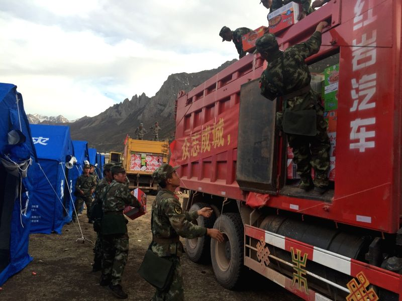 QAMDO, May 13, 2016 - Cellphone photo taken on May 12, 2016 shows armed police soldiers unloading disaster relief materials at earthquake-stricken area in Guodong Village, Dengqen County in southwest ...
