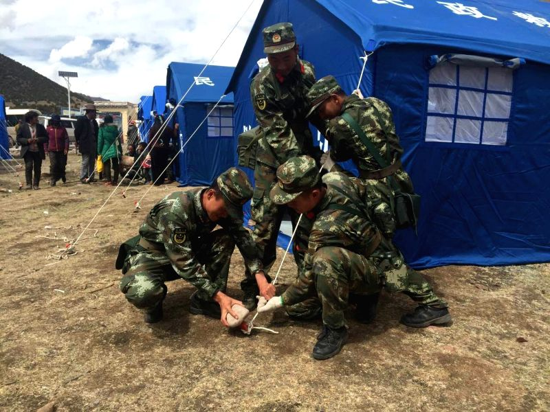 QAMDO, May 13, 2016 - Cellphone photo taken on May 12, 2016 shows armed police soldiers putting up tents in earthquake-stricken area in Guodong Village, Dengqen County in southwest China's Tibet ...
