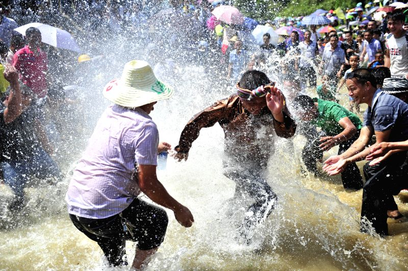 "People play in the water during the ""Naoyu"" Festival in Congjiang County in Qiandongnan Miao and Dong Autonomous Perfecture, southwest China's Guizhou"