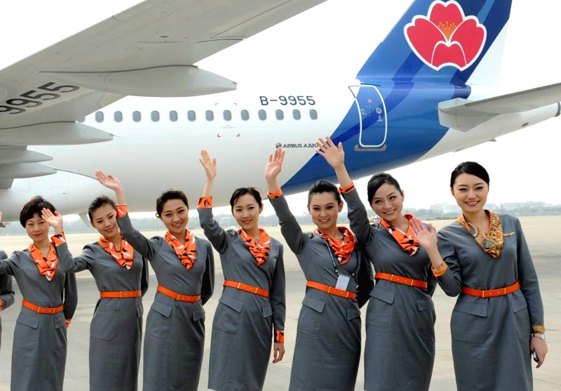 Crew members pose with an Airbus A320 in Qingdao, east China's Shandong Province, April 11, 2014. An Airbus A320, the first airplane of Qingdao Airlines, arrived ..