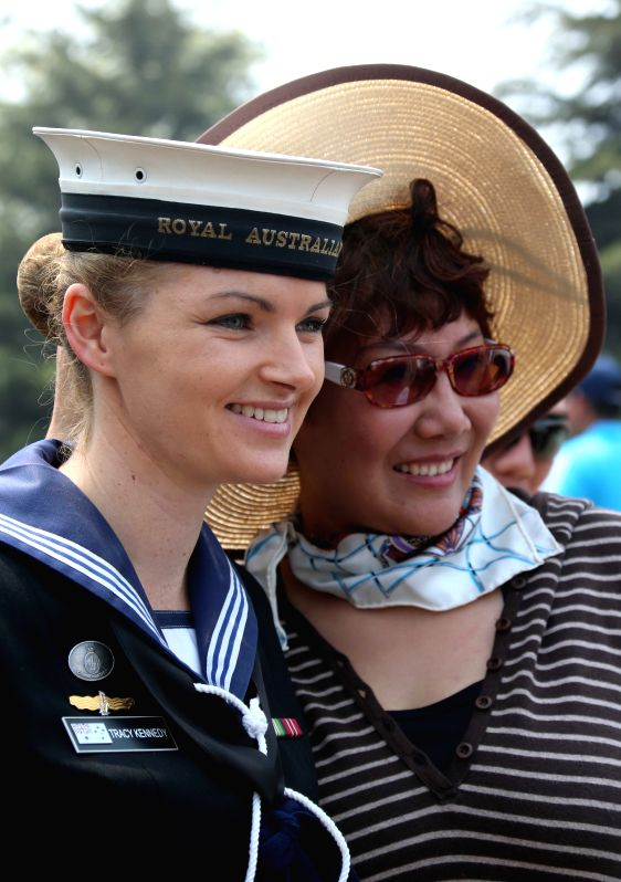 A member of the Australian naval band (L) poses for a photo with a visitor at the Dagang Port in Qingdao, east China's Shandong Province, April 22, 2014. Chinese ..