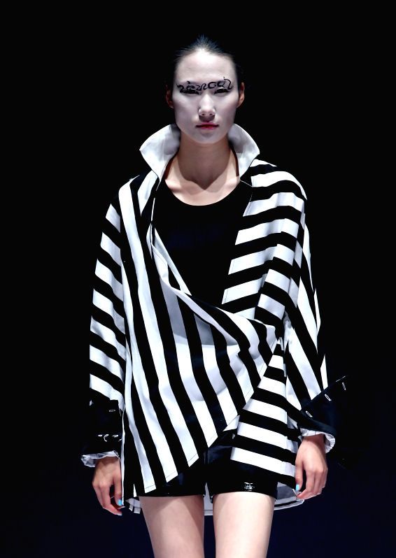 A model presents a creation by designer Xie Liwei during the China (Qingdao) International Fashion Week in Qingdao, east China's Shandong Province, April 24, 2015. ...