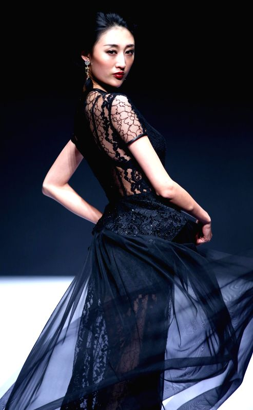 A model presents a creation by designer Zhang Yihua during the China (Qingdao) International Fashion Week in Qingdao, east China's Shandong Province, April 24, ...