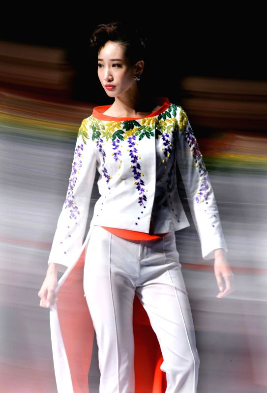 Photo taken using multiple exposure skill shows a model presents a creation during the 2014 China (Qingdao) International Fashion Week in Qingdao, east China's ...